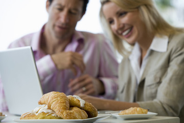 Business colleagues sitting at table, using laptop, smiling, focus on croissants in foreground