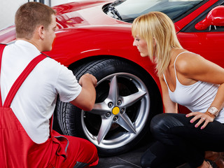 Customer and mechanic checking the tyre