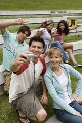Teenage boy (17-19) taking photograph with digital camera, friends making peace signs, smiling