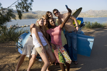 Teenagers (17-19) standing beside car with surfboard, girl taking photograph with camera phone