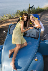 Teenage girls (17-19) listening to MP3 player on car bonnet, sharing headphones, elevated view