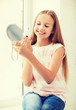 teenage girl with lip gloss and mirror