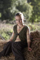 Girl (9-11) sitting on hay, smiling, portrait