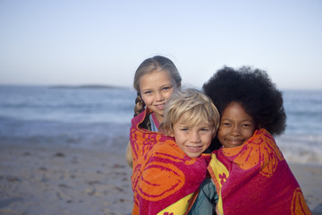 Three children (6-9) standing on beach, wrapped in towel, smiling, front view, portrait