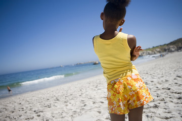 Girl (9-11) in yellow vest and shorts standing on beach, looking at sea, rear view (tilt)