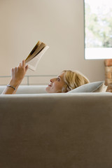 Woman relaxing on sofa at home, reading book, smiling, profile