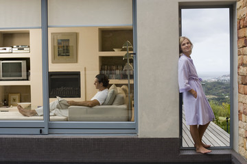 Couple relaxing at home, man on sofa, woman standing on balcony, leaning against wall, side view