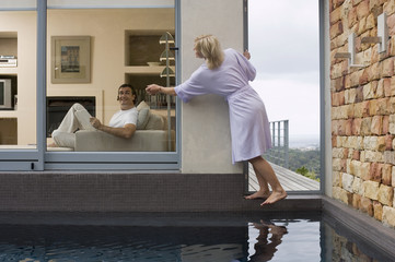 Couple relaxing at home, man on sofa, woman standing on balcony, tapping against window