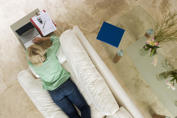 Woman lying on sofa at home, using laptop resting on coffee table, overhead view