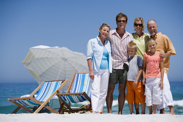 Multi-generational family standing on beach beside deckchairs, smiling, front view, portrait