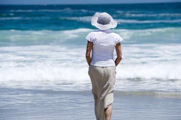 Woman in sun hat walking in surf at beach, face obscured, rear view