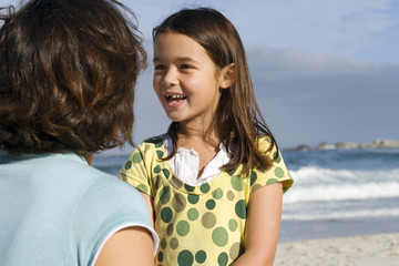 Mother and daughter (6-8) standing on beach, face to face, laughing