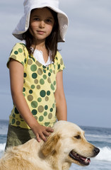 Girl (6-8) in sun hat standing on beach with dog, smiling, side view, portrait
