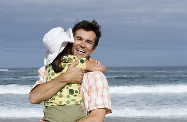 Father embracing daughter (6-8) on beach, smiling, sea in background