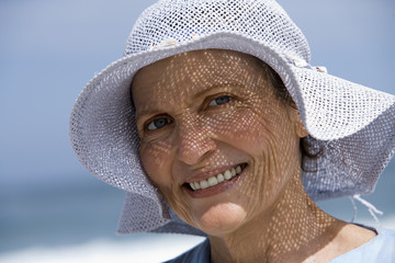 Senior woman wearing sun hat standing on beach, smiling, close-up, portrait