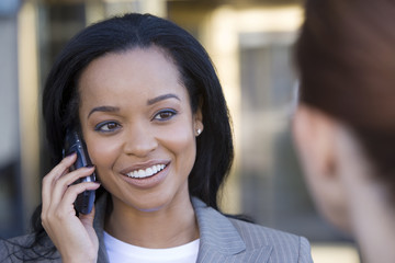 Businesswoman using mobile phone, outdoors, smiling, close-up (differential focus)