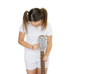 Girl in pigtails tuning guitar