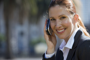 Businesswoman using mobile phone, outdoors, smiling, side view, portrait