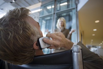 Businessman sitting in waiting area, using mobile phone, low angle view, rear view
