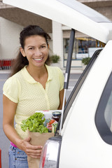 Woman loading car with grocery bags in supermarket car park, smiling, portrait