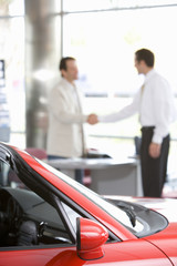 Salesman shaking hands with male customer in car showroom, focus on red convertible in foreground