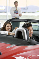 Couple sitting in red convertible in car showroom, salesman in background, smiling, portrait