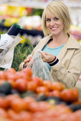 Woman shopping in grocery section of supermarket, putting tomatoes in plastic bag, smiling, portrait