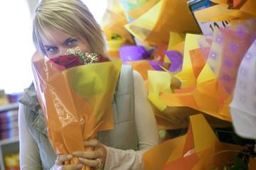 Woman smelling flower bouquet beside shop display in florists, face obscured, portrait