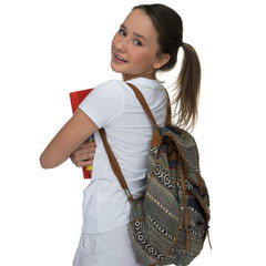 Young schoolgirl carrying a book and backpack