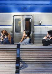 Three business people using mobile phones on railway platform beside stationary passenger train, profile