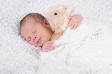 Newborn hält Kuscheltier und lächelt