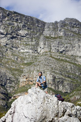 Mature man hiking on mountain trail, crouching on rock, looking at scenery, smiling, side view