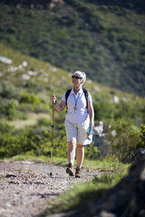 Mature woman hiking on mountain trail, carrying rucksack, using hiking pole, smiling, front view