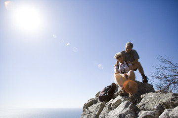 Mature hikers resting on clifftop edge overlooking Atlantic Ocean in bright sunlight, smiling, portrait