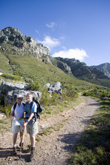 Mature couple, with rucksacks, hiking on mountain trail, woman using compass, man leaning on hiking pole, smiling