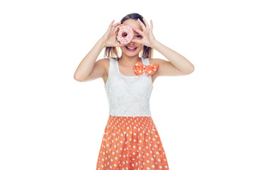Laughing young girl holding a donut to her eye
