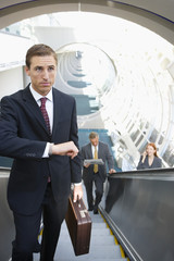 Businessman, with briefcase, standing on escalator, checking time on wristwatch, elevated view