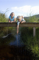 Boy (6-8) and girl (7-9) lying on small wooden footbridge above stream, holding sticks, smiling, portrait