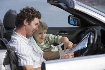 Father and son (6-8) sitting in convertible car, looking at road map, smiling, side view