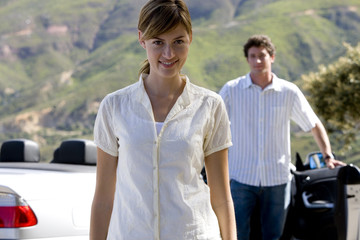 Couple standing beside parked convertible car on mountain roadside, focus on woman, smiling, portrait