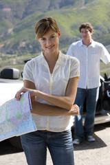Couple standing beside parked convertible car on mountain roadside, focus on woman holding map, smiling, portrait