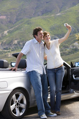 Couple standing beside parked convertible car on mountain roadside, woman taking self-portrait with camera