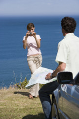 Couple standing on clifftop overlooking Atlantic Ocean, woman photographing man with map beside car