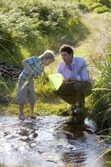 Father and son (6-8) fishing in shallow stream, boy looking in fishing net, side view