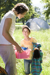Mother and daughter (8-10) unloading car on camping trip, woman carrying pink container, smiling