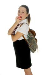 Young schoolgirl standing eating an apple