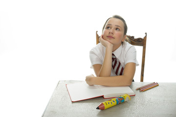 Bored young schoolgirl sitting daydreaming