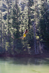 Man, in yellow swimming shorts, swinging on rope above lake, side view