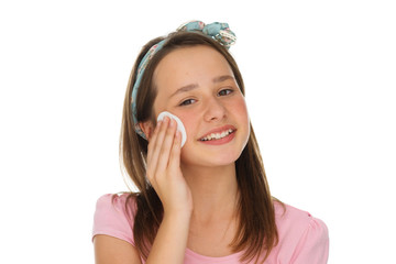Young girl cleaning her face with a cotton pad
