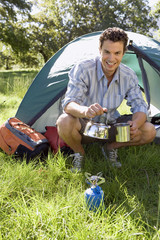 Young man crouching beside dome tent in woodland clearing, taking boiled kettle from camping stove, smiling, portrait